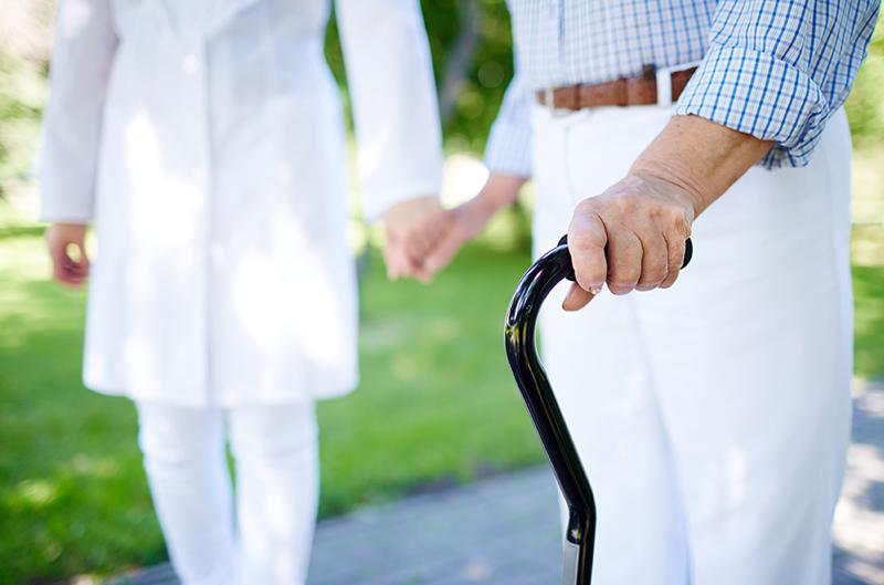 Immagine di un anziano con bastone accompagnato